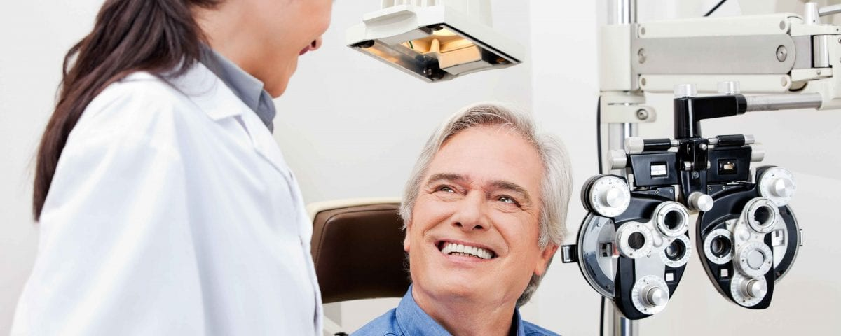 Smiling mature patient consulting with optometrist for an eye checkup